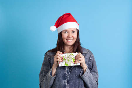 close up of a happy Asian young woman in a Santa hat holding a green gift box, on a blue background Stock fotó