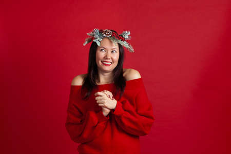 portrait of joyous laughing Asian young woman in ecstasy clasps her hands to chest and looks away, on a red background Stock fotó