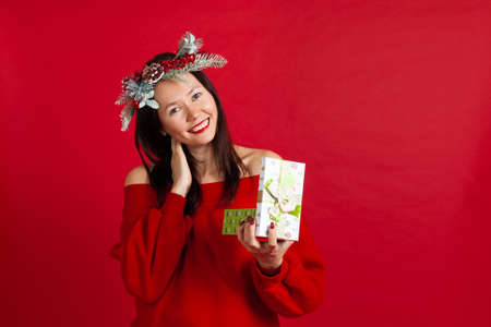 close up portrait of a laughing Asian young woman in a Christmas wreath with red lipstick enjoying a new years gift Stock fotó