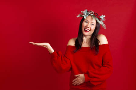 mock up of a happy laughing Asian young woman with a palm on which you can put something, on a red background Stock fotó