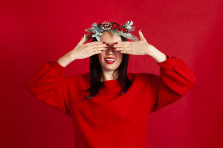 close-up portrait of surprised and excited Asian young woman in wreath covering her eyes with hands, on a red background