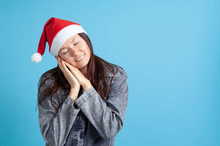 smiling Asian young woman in Santa Claus hat put her hands under her head, eyes closed and sleeping, on blue background