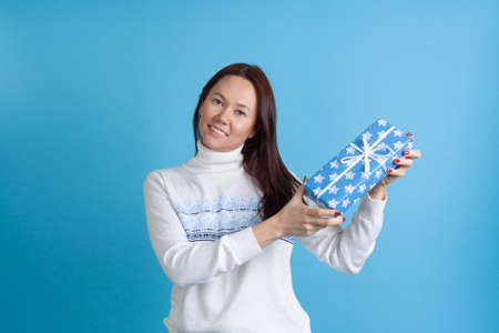 mock up smiling Asian young woman in sweater with snowflakes beautifully showing a gift box isolated on blue background Stock fotó
