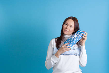 smiling Asian young woman in a sweater with snowflakes shakes a gift box near her head, isolated on a blue background