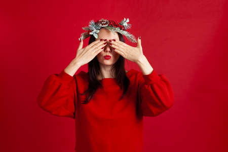 close-up portrait of Asian young woman in a wreath covering her eyes with her hands and blowing kiss, on red background