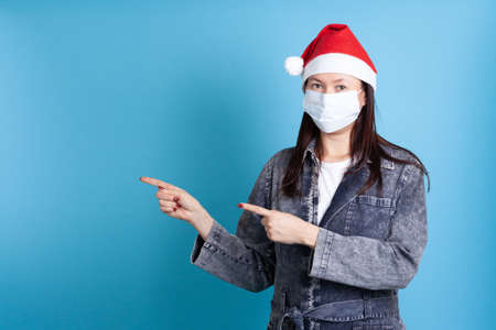 an Asian woman wearing Santa hat and medical protective mask against virus, points with index fingers at empty space