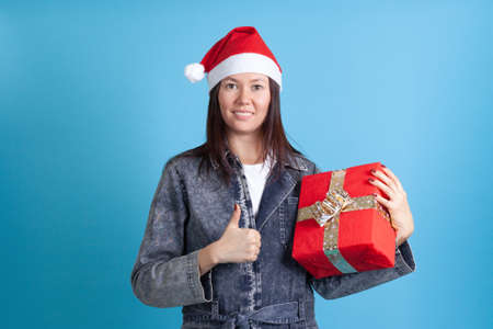 mock up smiling Asian young woman in Santa Claus hat holding red box and giving thumbs up isolated on blue background