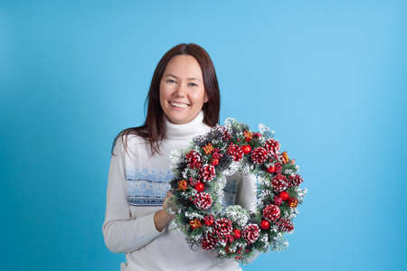 laughing Asian young woman holds Christmas wreath made of tree branches, cones and ornaments isolated on blue background