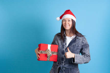 mock up of happy Asian young woman in Santa Claus hat holding a red gift box and giving a thumbs up on a blue background