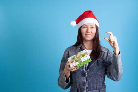 smiling Asian young woman in hat of Santa Claus showing fingers small size of the gift, the size doesnt matter Stock fotó
