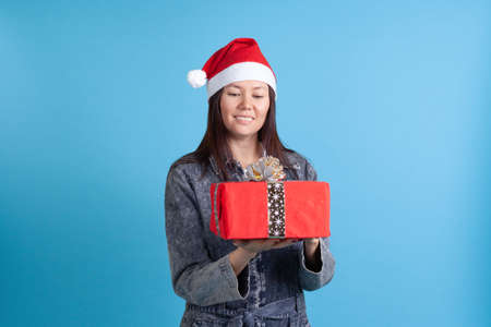 mock up smiling Asian young woman in Santa Claus hat looking at red gift box isolated on blue background Stock fotó