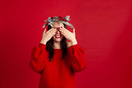 close-up portrait of a happily laughing Asian young woman in a wreath covering her eyes with her hands waiting for a gift and a new years miracle,