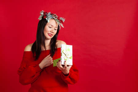mock up of beautiful Asian young woman in Christmas wreath with red lipstick opens a new year gift, on a red background