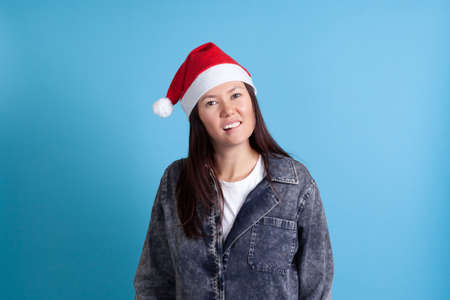 mock up of a serious, sexy Asian young woman in a Santa hat biting her lip with her teeth on a blue background Stock fotó