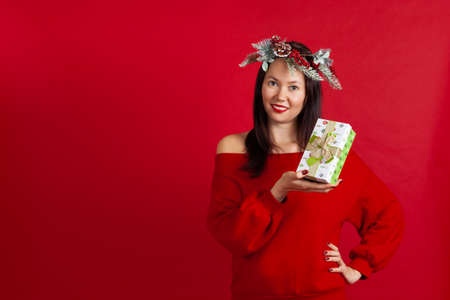 mock up of a beautiful Asian young woman in a Christmas wreath holding a green gift box on a red background