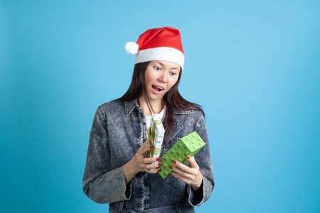 surprised Asian young woman in Santa Claus hat opens new year gift box, on blue background