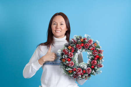 smiling Asian young woman holding Christmas wreath and thumbs up isolated on blue background