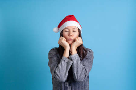 mock up of a serious, sad Asian young woman in a Santa Claus hat puts her head on her clenched hands and blows a kiss