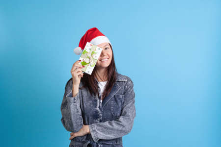 laughing Asian young woman in a Christmas wreath hiding one eye behind a gift box, on a blue background