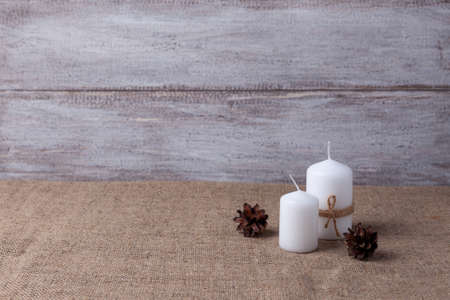 mock up of two white candles in jute rope, cones on a wooden background and burlap