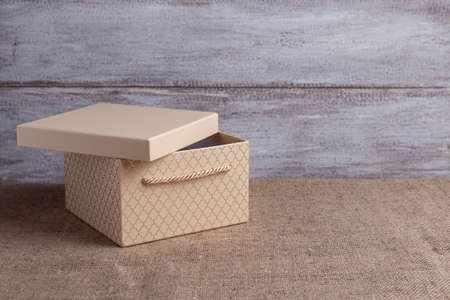 mock up of a beige gift box with an open lid on a wooden background Stock fotó