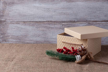 postcard from beige gift box with open lid and sprig of Christmas tree with decorations on wooden background and burlap Stock fotó