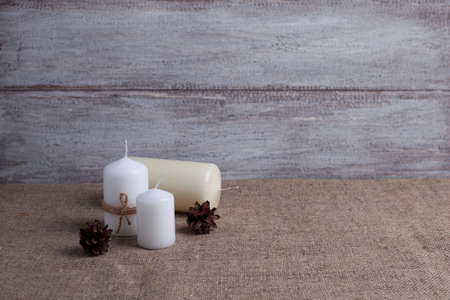 mock up of two white candles in jute rope and a vanilla candle on the side, cones on a wooden background and burlap Stock fotó