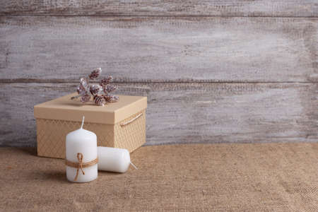 mock up of two white candles in a jute rope and beige gift box, cones on a wooden background Stock fotó