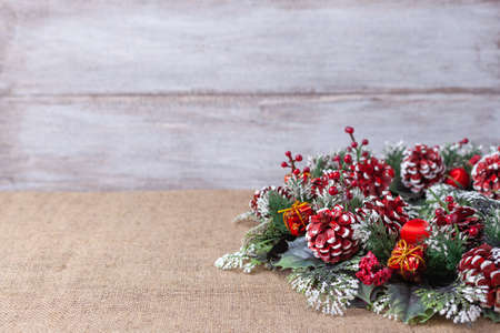 postcard of a homemade Christmas wreath of Christmas trees, cones, balls and berries on a wooden background Stock fotó