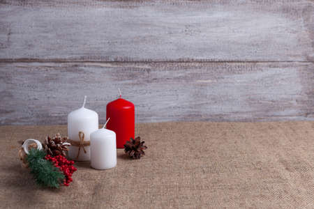 mock up of two white candles in jute rope and a red candle, cones, a sprig of a Christmas tree decorated with berries