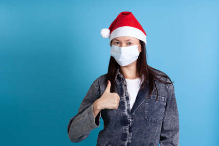 Asian woman wearing a Santa Claus hat and a medical covid-19 protective mask showing a thumbs up on a blue background