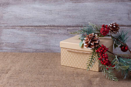 postcard from beige gift box and homemade Christmas wreath with cones, berries and balls on wooden background and burlap Stock fotó