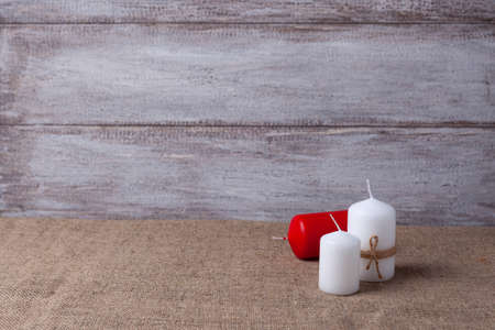 mock up of two white candles in jute rope and a red candle, cones on a wooden background
