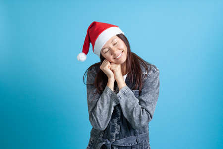 smiling Asian young woman in Santa Claus hat clenched her fists and put her hands under her head, eyes closed and asleep
