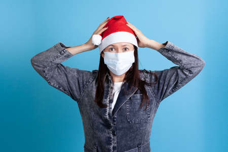 scared upset Asian woman wearing Santa hat and medical protective mask against the virus, holding her head with hands