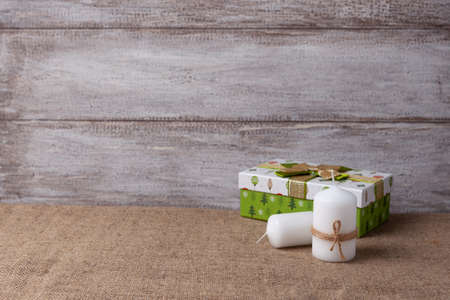 postcard of two white candles in a jute rope and a green gift box, on a wooden background
