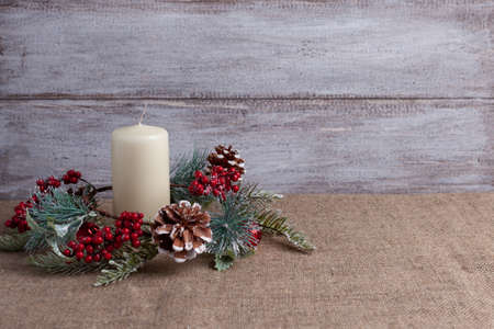 postcard of vanilla candle and homemade Christmas wreath with cones, berries and balls on a wooden background and burlap Stock fotó