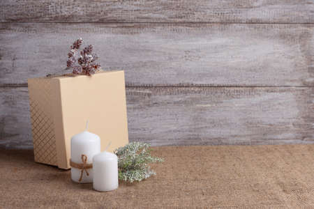 mock-up of two white candles in a jute rope and beige gift box, cones, sprig of lichen yagel on a wooden background