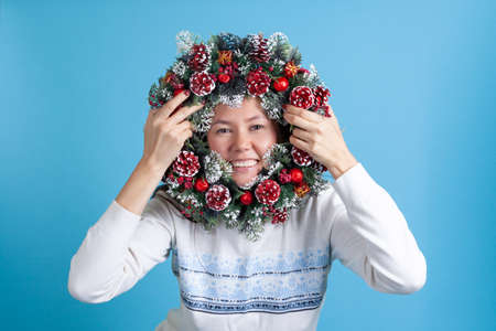 portrait of an Asian young woman looking through a Christmas wreath of tree branches, cones and ornaments