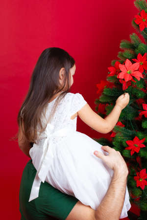 dad puts his daughter on his shoulder and helps decorate the Christmas tree with flowers, isolated on a red background Stock fotó