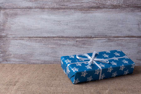 Christmas card from a blue gift box with white stars on a wooden background, minimalism style Stock fotó