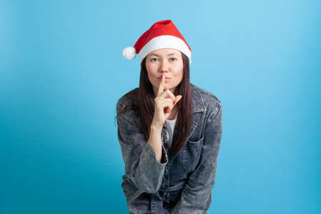 mock up portrait of a smiling Asian young woman in a Santa Claus hat puts her finger to her lips and asks for silence Stock fotó