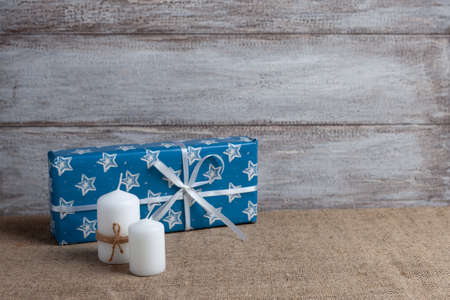 mock up of two white candles in jute rope and a blue gift box with snowflakes or stars, cones on a wooden background