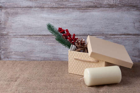 mock-up of beige gift box, Christmas tree branch with decorations, vanilla candle on a wooden background