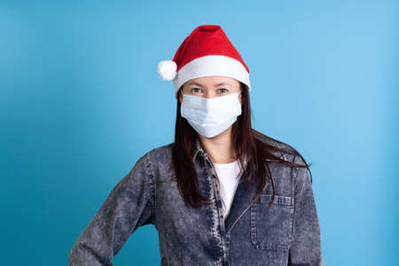 mock up of Asian young woman wearing a Santa Claus hat and a medical protective mask from covid-19 on a blue background