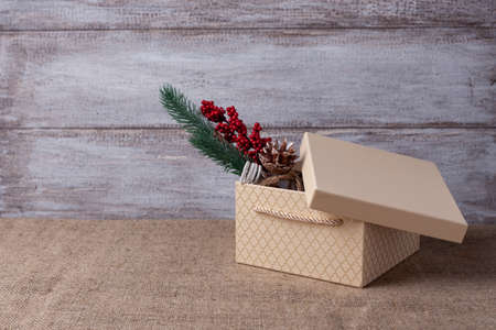 mock up of beige gift box with open lid and sprig of a Christmas tree with decorations inside it on a wooden background Stock fotó
