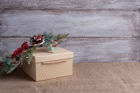 postcard from a beige gift box and a Christmas wreath with cones, berries and balls on a wooden background and burlap Stock fotó