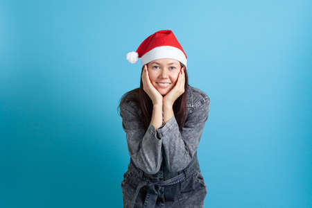 mock up portrait of a smiling Asian young woman in a Santa hat with her head in her hands, on a blue background Stock fotó