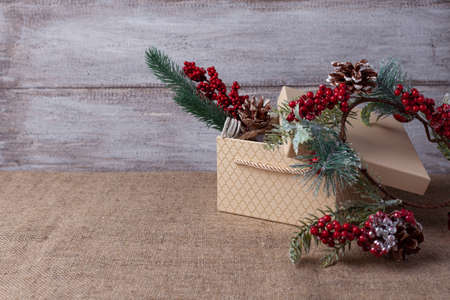 a card made of a beige gift box and a Christmas tree branch with decorations on a wooden background and burlap