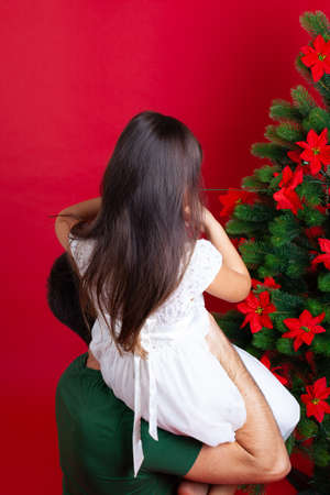 dad holds a girl in his arms helps decorate the Christmas tree with flowers, isolated on a red background Stock fotó